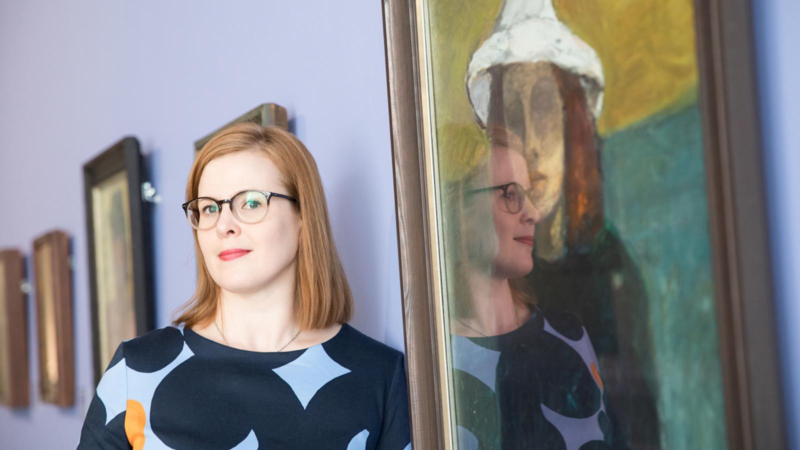 Kuvassa on Anu-Maarit Moilanen vieressään taulu, jossa on hatullinen nainen.